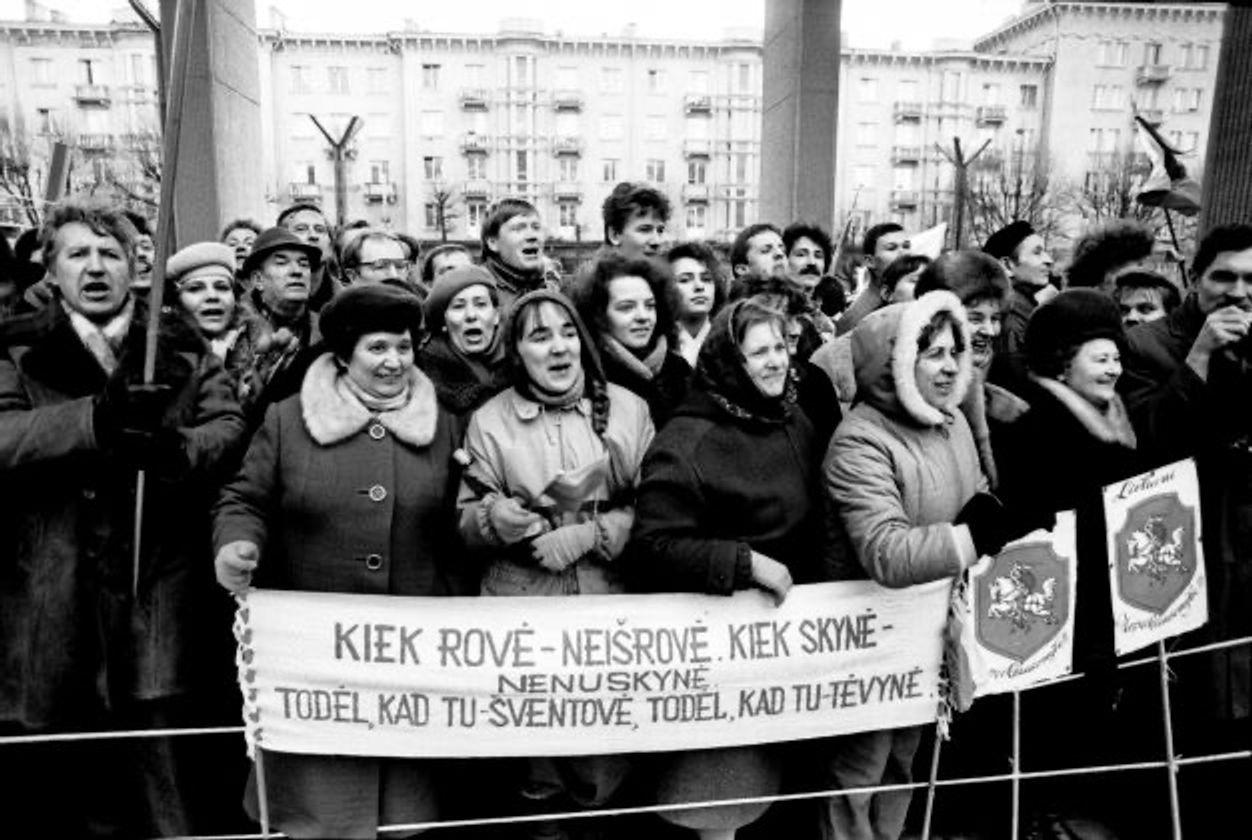 Демонстранты у Сейма держат плакат со словами из патриотической песни «Колыбельная Родине и матери»